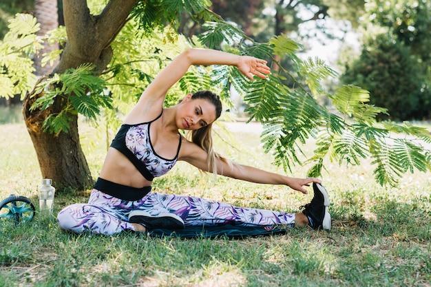 Portret van een jonge vrouw die uitrekkende oefening onder de boom doet Gratis Foto