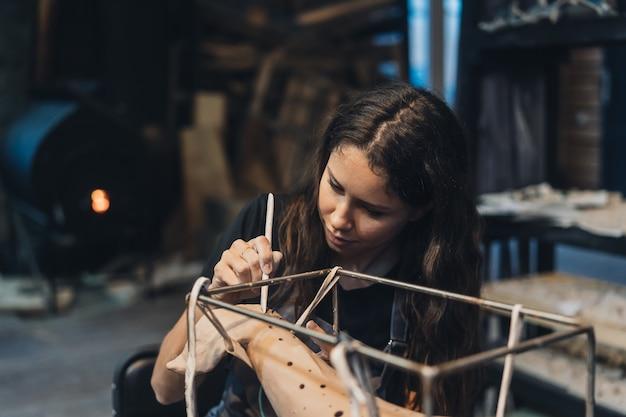 Portret van een jonge vrouw die van favoriete baan in workshop geniet. de pottenbakker werkt zorgvuldig aan de kleiwalvis Gratis Foto