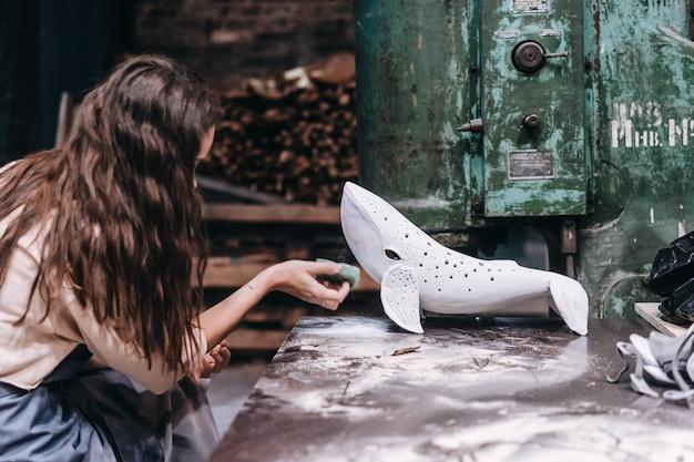 Portret van een jonge vrouw die van favoriete baan in workshop geniet. pottenbakker werkt zorgvuldig aan de keramische walvis Gratis Foto