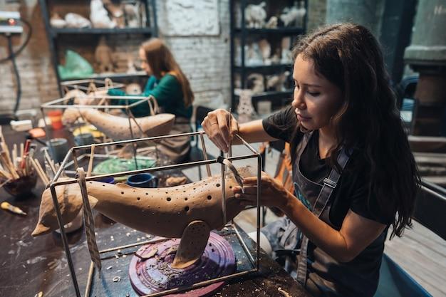 Portret van een jonge vrouw die van favoriete baan in workshop geniet. pottenbakker werkt zorgvuldig aan de kleiwalvis Gratis Foto