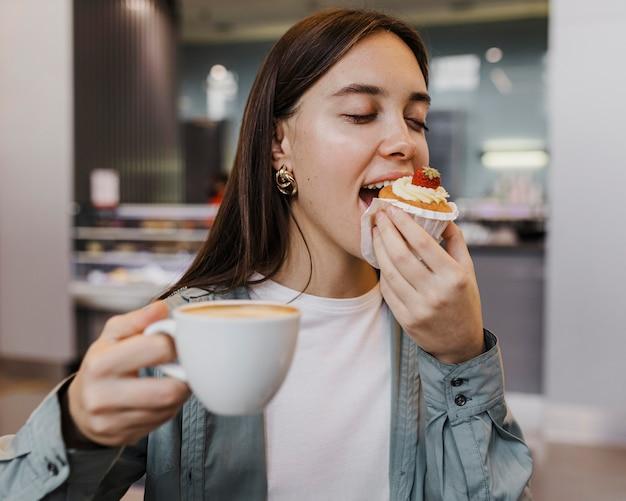 Portret van een jonge vrouw die van koffie en cake geniet Premium Foto