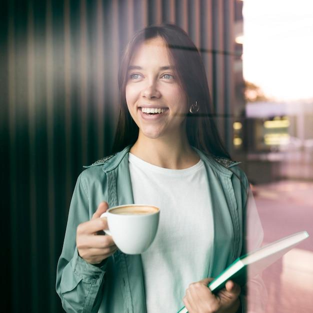 Portret van een jonge vrouw die van koffie geniet Gratis Foto