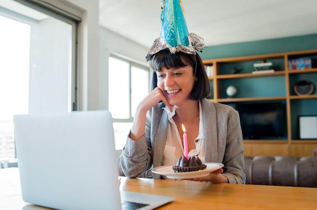 Portret van een jonge vrouw die verjaardag viert tijdens een videogesprek met laptop en cake van huis Premium Foto