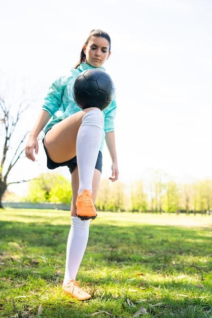 Portret van een jonge vrouw die voetbalvaardigheden oefent en trucs doet met de voetbalbal Gratis Foto