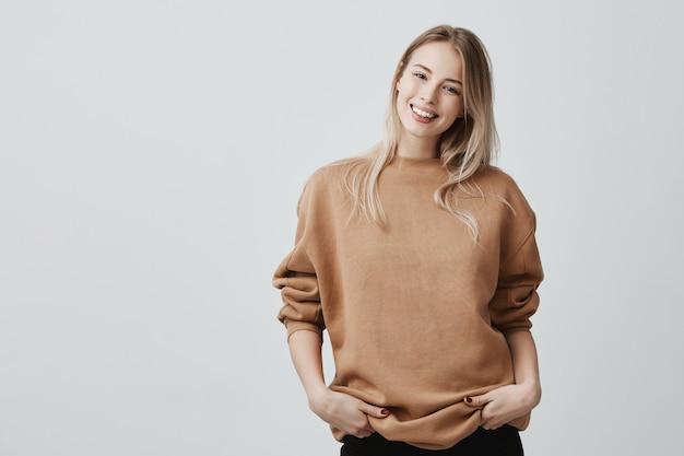 Portret van een jonge vrouw in casual kleding met blond geverfd haar, zachtjes glimlachend tijdens een aangenaam gesprek, staande in gesloten houding Gratis Foto