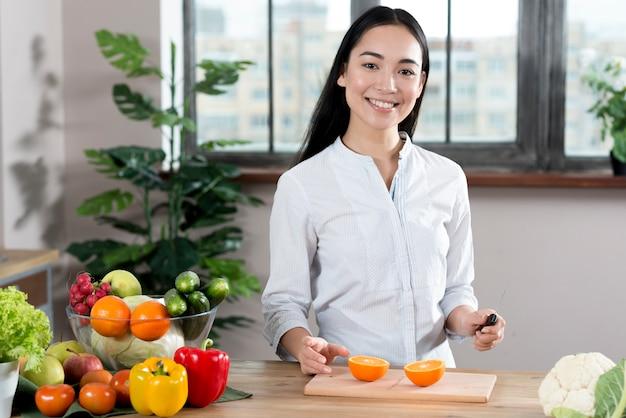 Portret van een jonge vrouw in de buurt van aanrecht met verschillende soorten groenten en fruit Gratis Foto