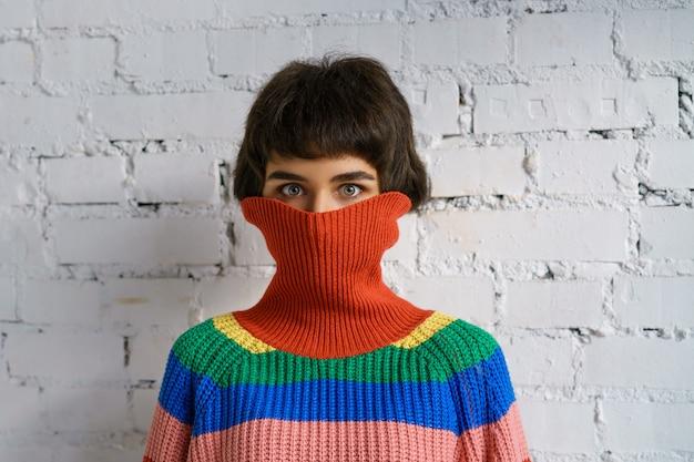 Portret van een jonge vrouw in een veelkleurige trui, die haar gezicht bedekt met een trui. het concept van verlegenheid Premium Foto