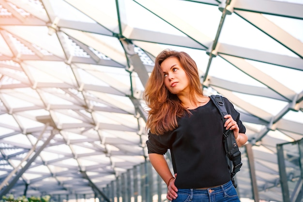 Portret van een jonge vrouw in een zakencentrum met een glazen plafond in de vorm van een honingraat Premium Foto