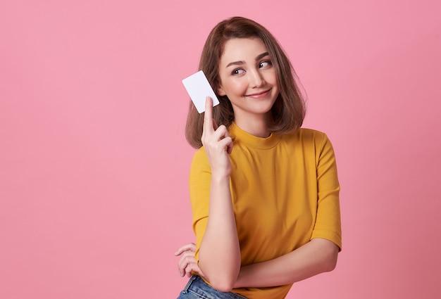 Portret van een jonge vrouw in geel shirt met een creditcard Premium Foto