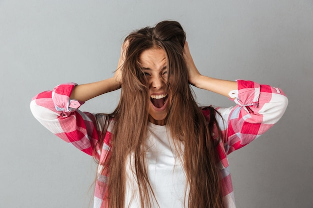 Portret van een jonge vrouw in het geruite overhemd gillen Gratis Foto