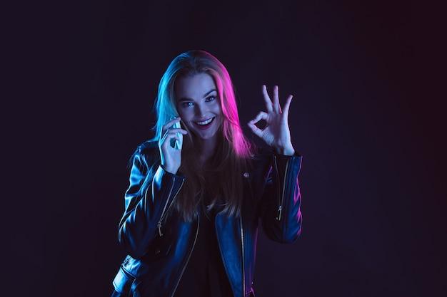 Portret van een jonge vrouw in neonlicht op donkere achtergrondkleur. Gratis Foto