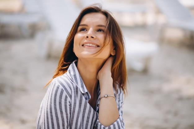 Portret van een jonge vrouw in shirt op het strand Gratis Foto