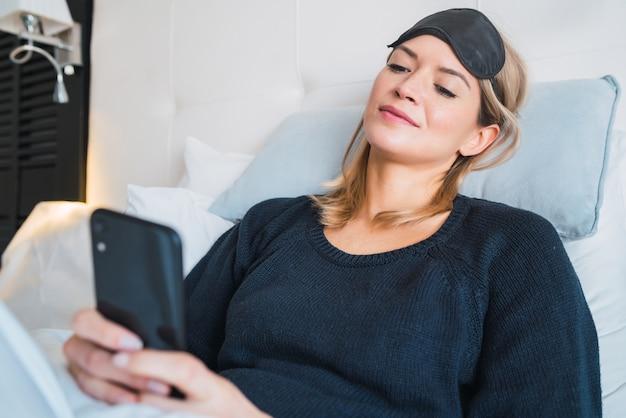 Portret van een jonge vrouw met behulp van haar mobiele telefoon terwijl het leggen op bed in hotelkamer. reis- en levensstijlconcept. Gratis Foto