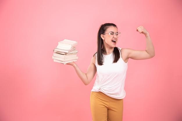 Portret van een jonge vrouw met een bril op roze met boeken in haar handen Gratis Foto