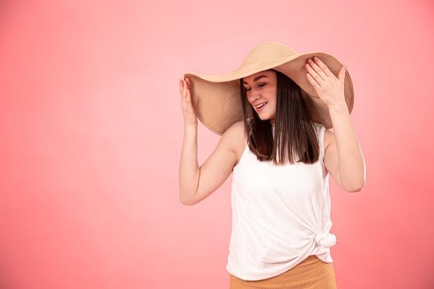 Portret van een jonge vrouw met een grote zomerhoed en een wit t-shirt, op een roze achtergrond. het concept van zomerse look. Gratis Foto