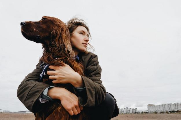 Portret van een jonge vrouw met haar hond. ierse setterhond in de armen van de liefhebbende minnares. Premium Foto