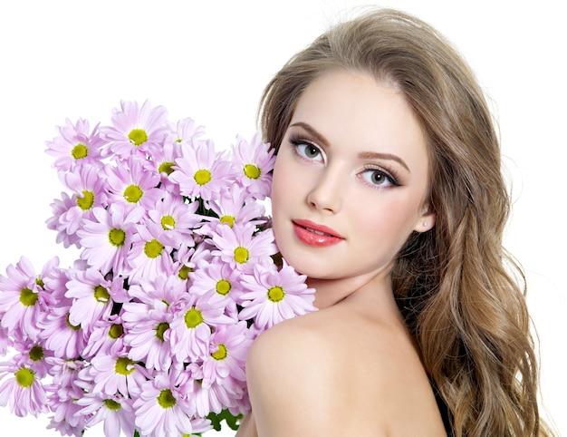 Portret van een jonge vrouw met prachtige lentebloemen op wit Gratis Foto