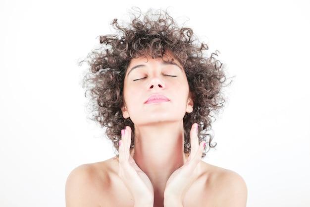 Portret van een jonge vrouw met schone huid en gesloten ogen geïsoleerd op een witte achtergrond Gratis Foto