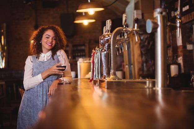 Portret van een jonge vrouw met wijn aan balie Premium Foto