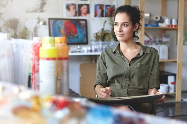 Portret van een jonge vrouw van creatieve bezetting zittend op een moderne werkplaats en werken, genietend van het proces van het creëren van iets moois, zijwaarts kijkend met tevreden geïnspireerde uitdrukking op haar gezicht Gratis Foto