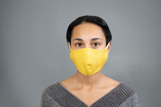 Portret van een jonge vrouw van gemengd ras met geel medisch masker close-up Premium Foto