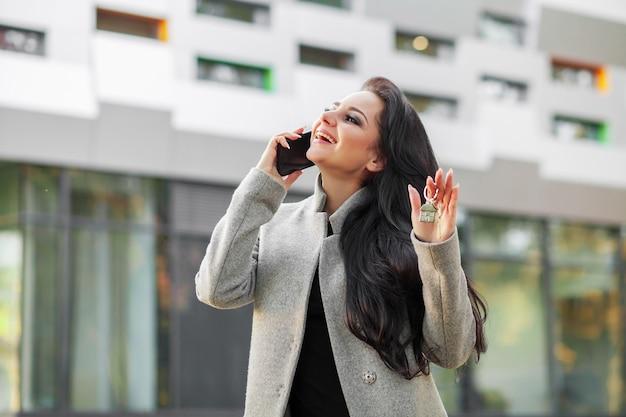 Portret van een jonge vrouwmakelaar of een onderneemster die zich in openlucht op het moderne woondistrict bevinden Premium Foto