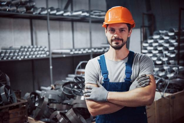 Portret van een jonge werknemer in een harde hoed bij een grote metaalbewerkingsfabriek. Gratis Foto