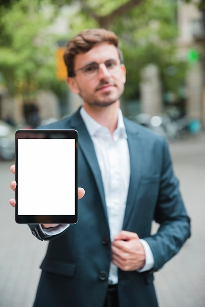 Portret van een jonge zakenman die de witte digitale tablet van de het schermvertoning toont Gratis Foto