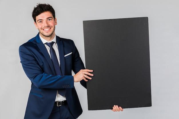 Portret van een jonge zakenman die leeg zwart aanplakbiljet houdt tegen grijze achtergrond Gratis Foto