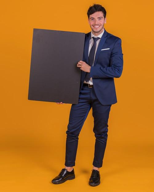 Portret van een jonge zakenman die leeg zwart aanplakbiljet op een oranje achtergrond houdt Gratis Foto
