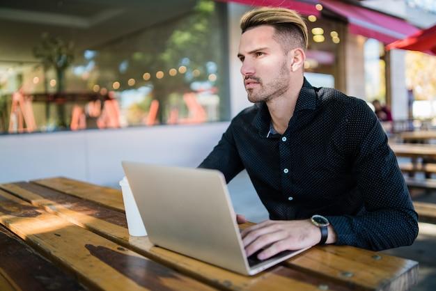 Portret van een jonge zakenman die op zijn laptop werkt terwijl hij in een coffeeshop zit. technologie en bedrijfsconcept. Gratis Foto