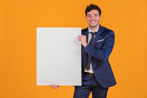 Portret van een jonge zakenman die wit leeg aanplakbiljet houdt tegen een oranje achtergrond Gratis Foto