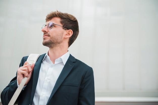Portret van een jonge zakenman draagtas op zijn schouder Gratis Foto