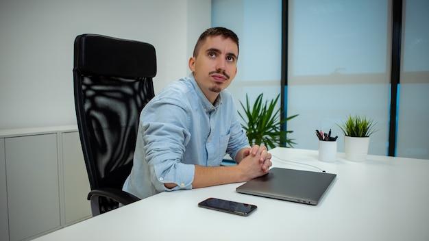 Portret van een jonge zakenman zit aan zijn bureau voor de computer op kantoor. zelfverzekerde ondernemer die met laptop aan een project werkt Premium Foto