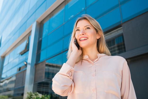Portret van een jonge zakenvrouw praten aan de telefoon terwijl je buiten kantoorgebouwen staat. bedrijfs- en succesconcept. Gratis Foto