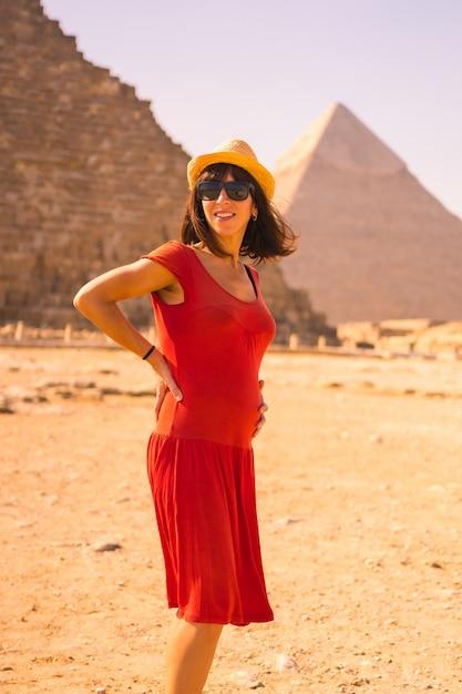 Portret van een jonge zwangere vrouw in rode jurk bij de piramide van cheops de grootste piramide. de piramides van gizeh zijn het oudste grafmonument ter wereld. in de stad caïro, egypte Premium Foto