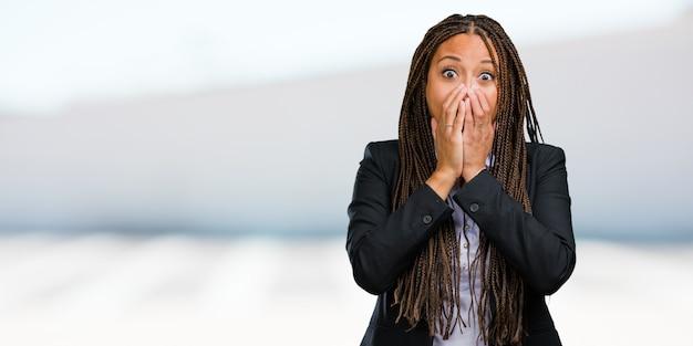 Portret van een jonge zwarte zakenvrouw erg bang en bang, wanhopig naar iets, schreeuwt van lijden en open ogen, concept van waanzin Premium Foto