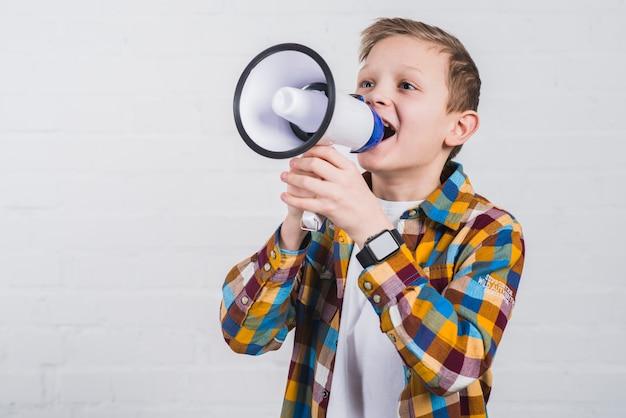 Portret van een jongen die door megafoon tegen witte bakstenen muur gilt Gratis Foto