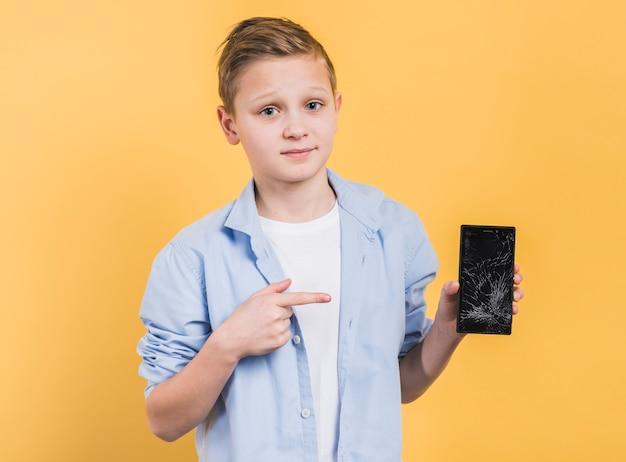 Portret van een jongen die gebroken smartphone met het verpletterde scherm tegen gele achtergrond toont Gratis Foto