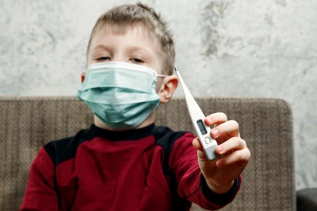 Portret van een jongen, een kind in een medisch masker houdt een thermometer in zijn handen Premium Foto