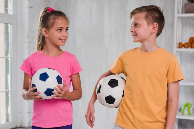 Portret van een jongen en meisje houden voetballen in de hand te kijken naar elkaar Gratis Foto