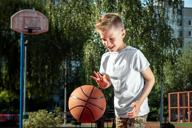 Portret van een jongen met een basketbal op een basketbalveld Premium Foto