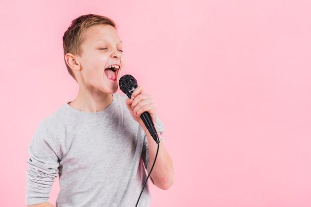 Portret van een jongen zingen lied op microfoon tegen roze achtergrond Gratis Foto