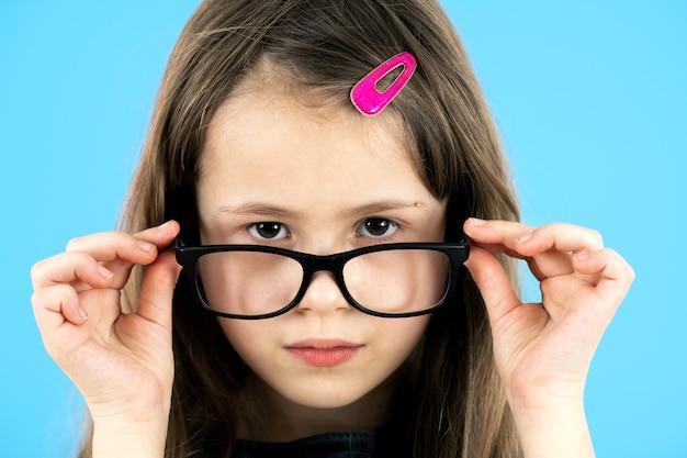 Portret van een kind school meisje close-up kijken bril geïsoleerd op blauw Premium Foto