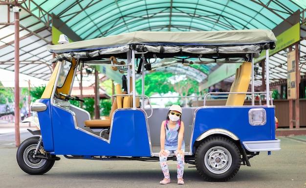 Portret van een klein aziatisch meisje dat masker en glb draagt die in tuk tuk-taxi zit Premium Foto