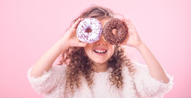 Portret van een klein glimlachend meisje met donuts Gratis Foto