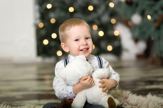 Portret van een klein jongensspel met teddybeer dichtbij een kerstboom. kerst versiering. de jongen verheugt zich op zijn kerstcadeau. vrolijk kerstfeest en een gelukkig nieuwjaar Premium Foto