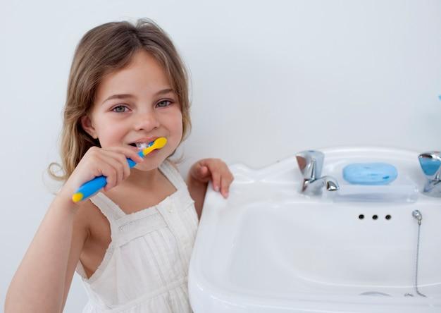 Portret van een klein meisje dat haar tanden schoonmaakt Premium Foto