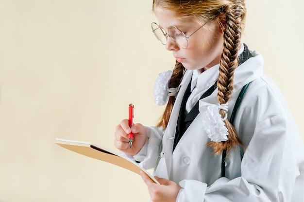 Portret van een klein meisje in de jas van een witte arts met een bril, documenten en een stethoscoop die naar de camera kijkt en glimlacht Premium Foto