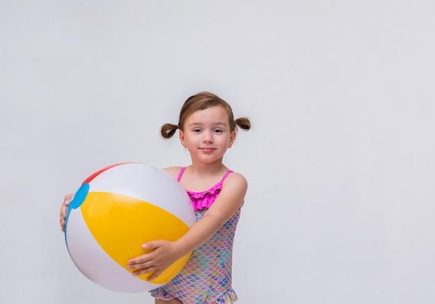 Portret van een klein meisje met paardestaarten in een zwempak met een opblaasbare bal op een geïsoleerd wit Premium Foto
